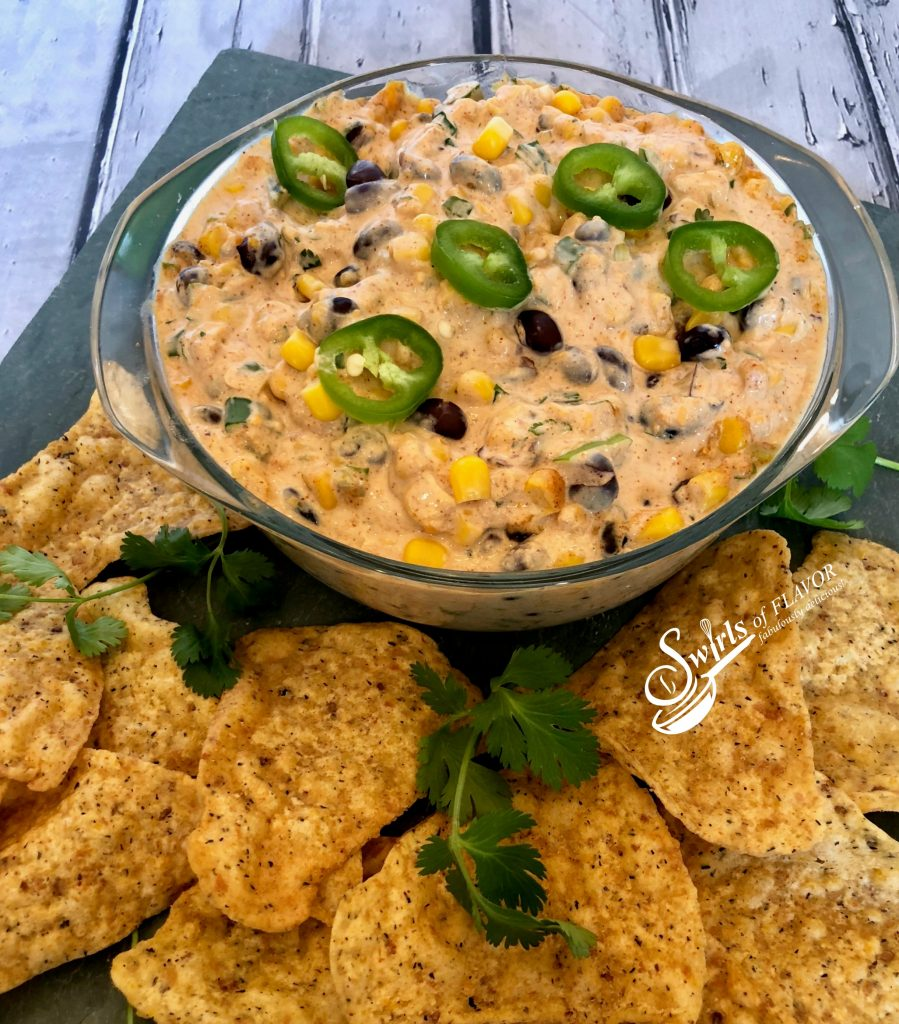 Creamy Corn and Black Bean Dip, an easy dip recipe that's bursting with cheesy goodness and a hint of spice, served with tortilla chips or fresh veggie dippers, is a delicious way to kick off your Cinco de Mayo fiesta! #easyrecipe #entertaining #hotdip #corn #blackbean #creamydip #appetizer #partyfood #gameday #swirlsofflavor